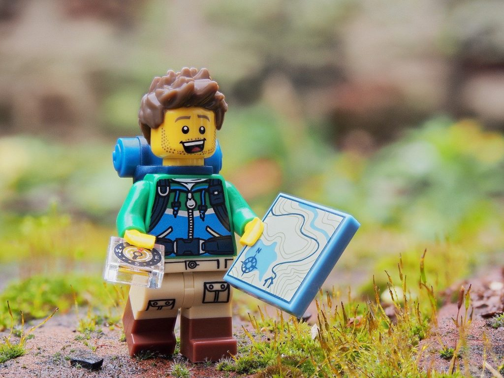 Lego figure of a person using map and compass